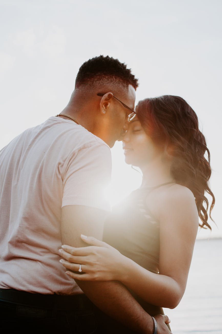 man wearing white shirt kissing woman in her nose